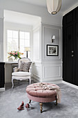 Stylish armchair with cushion and round pouffe in dressing room