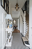 Console table on chequered floor in hallway with staircase