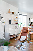 Retro armchair in front of String shelving in Scandinavian-style living room