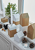 Simple house-shaped ornaments and wooden candle holders on windowsill