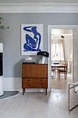 Art print above retro bureau in living room with stucco frieze