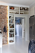 Fitted shelves around door next to exposed brick wall in kitchen