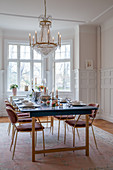 Velvet chairs around festively set dining table in glamorous dining room