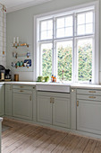 Classic, elegant kitchen in period building with shallow sink below window