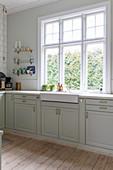 Elegante, klassische Küche im Altbau mit Spülstein unterm Fenster