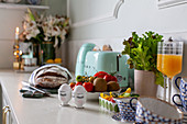 Boiled eggs, bread, juice, fruit and crockery on kitchen worktop