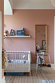 Cot and small clothes rack in nursery with pink wall