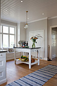 Island counter in white, spacious country-house kitchen with windowseat