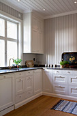 White, spacious country-house kitchen with wood-panelled walls