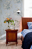 Antique bedside cabinet next to wooden bed in bedroom with vintage-style floral wallpaper