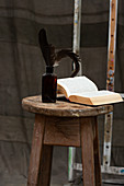 Open book and feathers in bottle on wooden stool