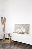 Sailing boat ornaments made from driftwood and fabric remnants next to stool and paddles in corner