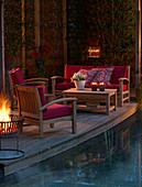 Lounge furniture on candlelit terrace next to pool at twilight