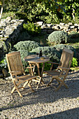 Wooden garden furniture in seating area of Mediterranean garden