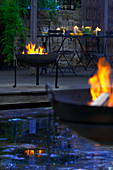 Fire bowls around pond in twilight garden