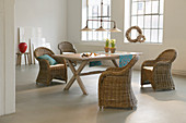 Wicker armchairs around dining table in loft apartment with factory-style windows