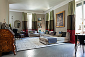 Pale sofa set and antique bureau in open-plan interior