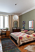 Patterned bedspread on double bed, chest of drawers, mirror and desk in bedroom