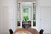 View through open, double, sliding doors with stained-glass inserts leading into living room