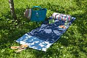 Bolster on hand-sewn sunbathing blanket on lawn