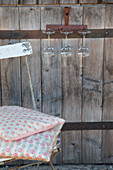 Old rusty rake used as glass rack on wooden door