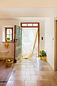 Batik curtain in open door leading into summery country house