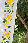 Yellow flowers and green leaves painted on white fabric