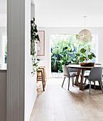 Runder Tisch mit Stühlen in offener Küche, im Hintergrund Terrasse