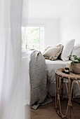 Rattan bedside table next to bed in white bedroom
