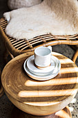Ceramic place setting on a round teak table next to a bamboo chair