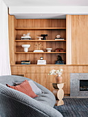 Built-in wooden wall unit in the living room with gray sofa