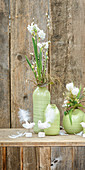 Spring flowers in green vases in front of rustic wooden wall