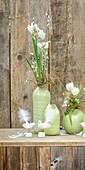 Grüne Vasen mit Frühlingssträußen vor rustikaler Holzwand
