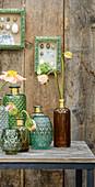 Frühlingsblumen in Reliefvasen vor Bretterwand mit Osterbildern