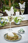 Butterfly-shaped place card on glass of Prosecco on Easter dining table