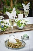 Schmetterling als Tischkarte am Sektglas auf dem Ostertisch