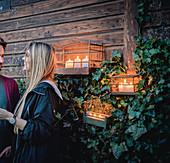 Smiling couple next to arrangement of candles in birdcages on outside wall of summer house