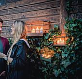 Lachendes Paar neben Kerzendeko in Vogelkäfigen am Gartenhaus