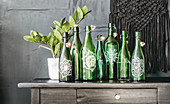 Arrangement of green glass bottles painted with mandalas