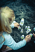 Girl playing with painted pebbles in sand