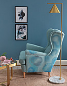 Watercolour effect on armchair upholstery painted with fabric paints against blue wall