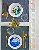 Teller in Aquarell-Optik und goldenes Besteck auf gedecktem Tisch