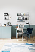 Dining table against two-tone wall next to kitchen in open-plan interior