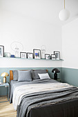 Picture ledge on two-tone wall in minimalist bedroom with clean lines