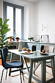 Set folding table in modern kitchen-dining room in blue and white