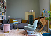 Deep-seat sofa, stool, armchair and wooden bureau in fifties-style living room