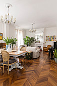 Dining table and herringbone parquet floor in open-plan living room of period building