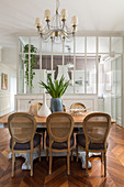 Medallion chairs around dining table in front of kitchen separated by glass wall in period building