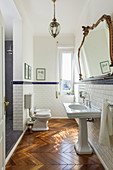 Classic bathroom with subway tiles and herringbone parquet floor in period building