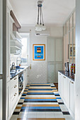 White cupboards, colourful tiled floor and subway tiles in kitchen